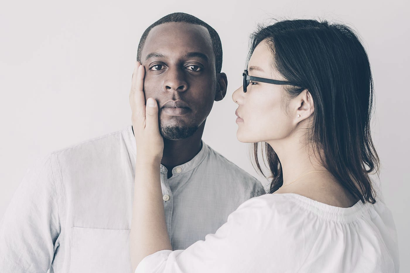 Serious Asian woman touching cheek of African boyfriend looking at camera